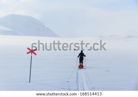 Cross country skier with pulka (sled) on a marked trail, Kungsleden, in Lapland, Sweden - stock photo