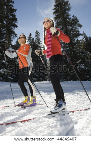 Cross country skiers smiling as they move through the snow. Vertical shot. - stock photo