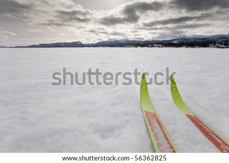 Cross country skiing. Skis in tracks on frozen lake with distant shoreline. Perfect winter snow conditions. - stock photo