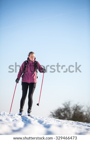 Cross-country skiing: young woman cross-country skiing on a snowy winter day - stock photo