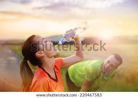 Cross-country trail running couple having water break at sunset - stock photo