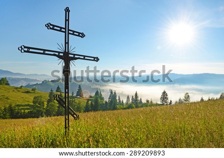 Cross-crucifixion in the field on a sunny day with fog in the mountains (pilgrimage, harmony, inspiration, peace - concept) - stock photo