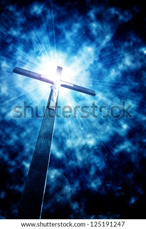 cross in sun rays against cloudy sky - stock photo