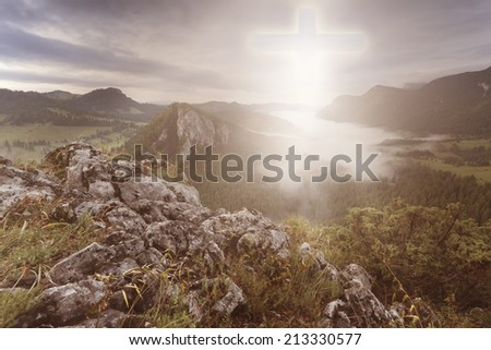 Cross in the sky with light shinning down seen from the top of a mountain - stock photo