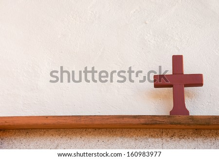 cross made of clay on a wooden board - stock photo