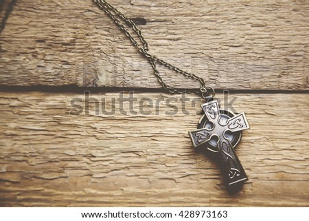 cross on the brown wooden table - stock photo