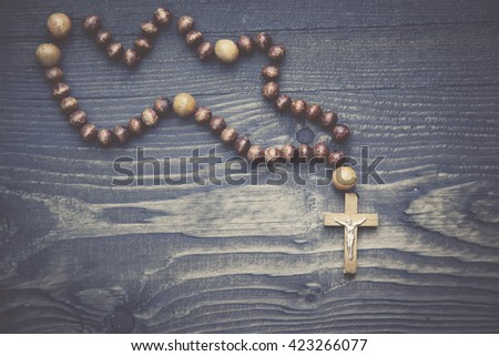 cross on the wooden table background - stock photo