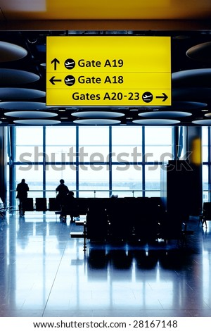 Cross process toned image of airport lounge with waiting people silhouettes. Heathrow airport, Great Britain. - stock photo
