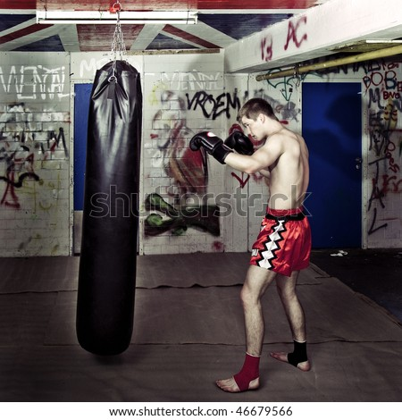 Cross processed image of a boxer practicing in a basement with a boxing bag - stock photo
