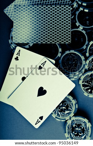 cross processed poker setup displaying aces on chips and cards - stock photo