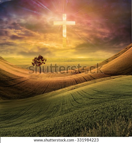 Cross radiates light in sky over beautiful landscape - stock photo