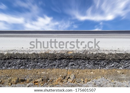 Cross section of asphalt road (top layer is an asphalt and bottom layer is an crushed rock ) with blue sky background. - stock photo