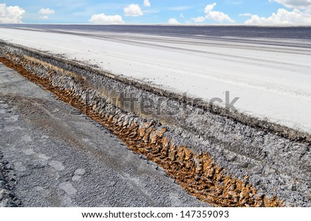 Cross section of asphalt road with sky background. - stock photo