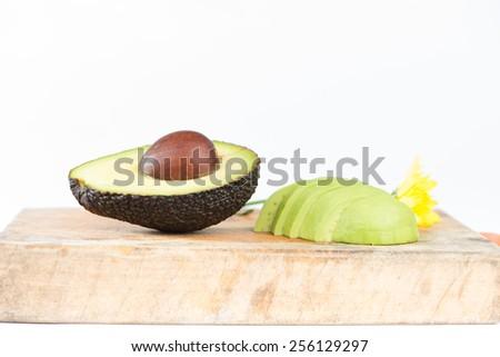 Cross section of Avocado fruit on wood - stock photo