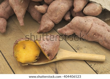 Cross section of Boiled potatoes on wooden ladle and a pile of purple sweet potatoes pouring out of burlap sack over wooden table - stock photo