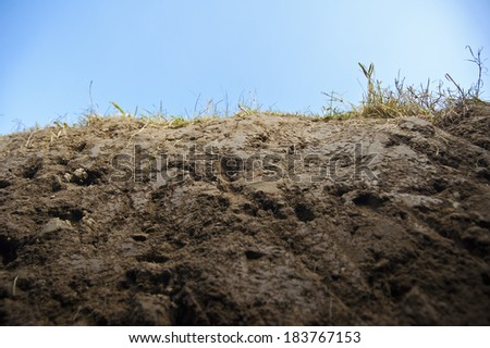 Cross section of earth with grass - closeup, frog view, cloudy sky behind. - stock photo