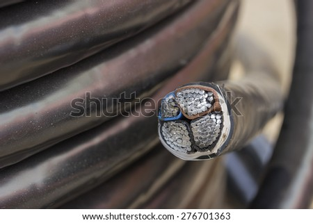 Cross section of electric black industrial underground cable on large wooden reel. Four core al cable. Selective focus and shallow dof. - stock photo