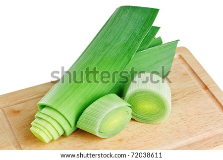 Cross-section of green leek on wooden chopping board isolated on white - stock photo