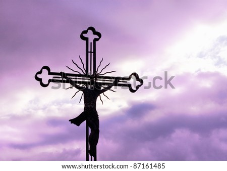 Cross silhouette against purple sky - stock photo