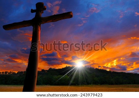 Cross Silhouette at the Sunset. Cross silhouette at the beautiful sunset over the hill with cloudy sky - stock photo