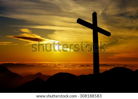 Cross silhouette over a dramatic sky at sunset - stock photo