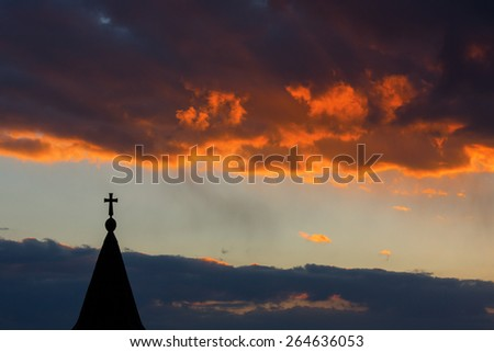 cross silhouette with the sunset as background and red clouds - stock photo