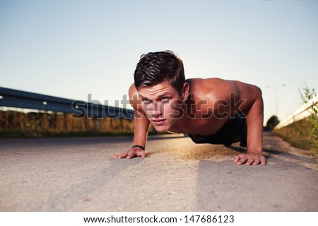 cross-training during sunset. Young man doing push ups. - stock photo