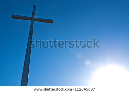 cross with sky and sun in the background - stock photo