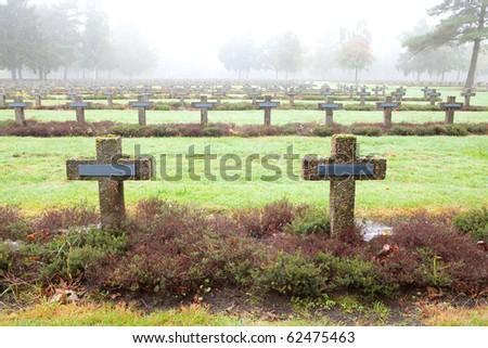 crosses at cemetery in autumn mist stone tombstones - stock photo