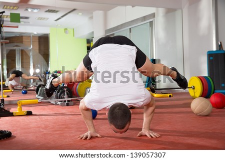 Crossfit fitness handstand push ups balance man workout at gym - stock photo