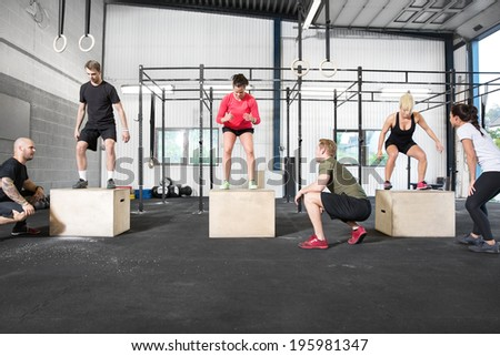Crossfit group trains box jump - stock photo
