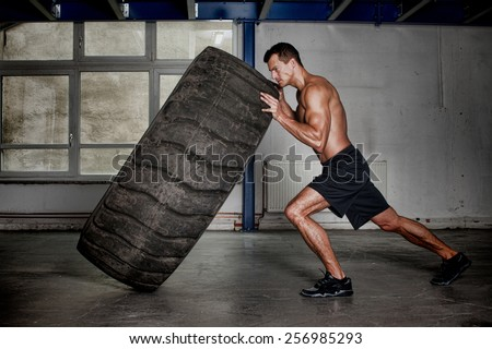crossfit training - man flipping tire - stock photo