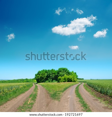 crossing of two rural road and deep blue sky - stock photo