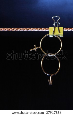 Crossing sex symbols made from brass wire hanging on dark background with rope - stock photo