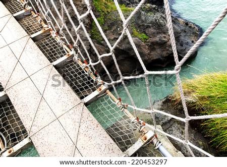 Crossing the rope bridge - stock photo
