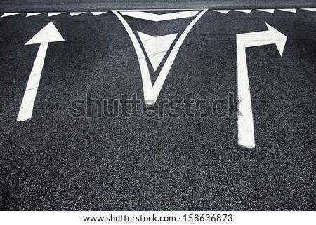 Crossroad choice sign symbols on asphalt. - stock photo