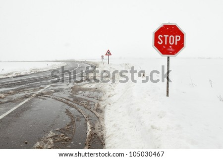 Crossroad in a stormy winter day with stop sign - stock photo