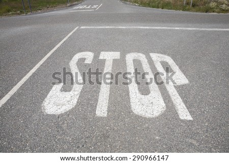crossroads with stop symbol text painted on asphalt in rural road next to Madrid Spain Europe - stock photo