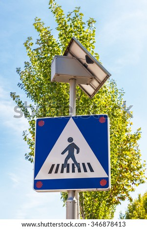 Crosswalk sign in red that is powered by solar energy with its own solar panel - stock photo