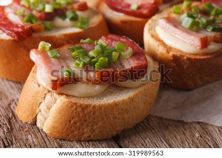 Crostini sandwiches with bacon and mozzarella cheese macro on the table. horizontal