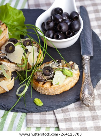 Crostini with fish with olives, cheese and chives - stock photo