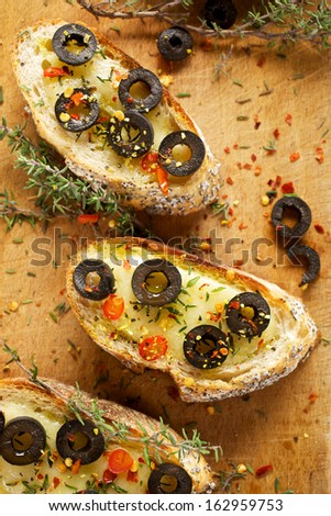 Crostini with mozzarella, black olives, chili peppers and fresh thyme - stock photo