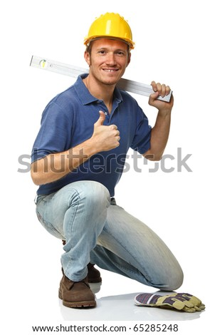 crouched handyman with spirit level isolated on white - stock photo