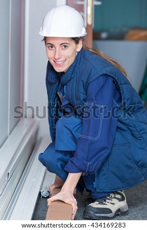 Crouched woman holding cardbord box - stock photo