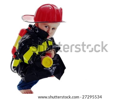 Crouching toddler fire fighter points water backpack sprayer at camera - stock photo