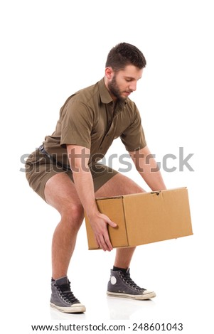 Crouching with a heavy package. Man in khaki uniform picking up heavy box. Full length studio shot isolated on white. - stock photo