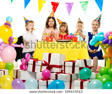 Croup of happy children celebrating birthday behind table  - stock photo