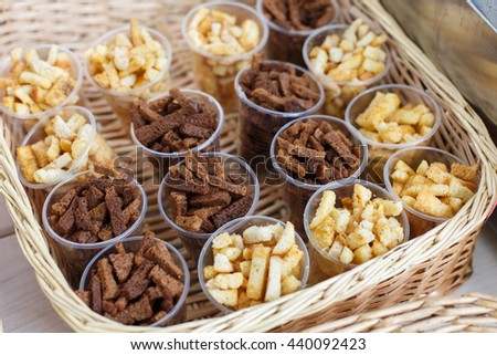 Croutons snack in plastic cups for party. Party snack lunch. Croutons crackers of white and brown whole grain bread. Many, plenty of beer snack in basket. - stock photo