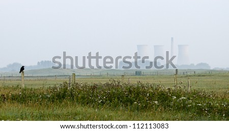 Crow sitting on fence with nuclear power plant in the background - stock photo