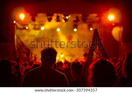 crowd at a concert in a red light, noise added - stock photo